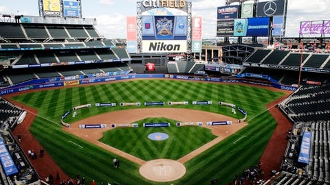 People walk on the field after a press conference about the NHL Winter Classic at Citi Field in New York, Friday, Sept. 8, 2017. The New York Rangers and Buffalo Sabres will play in the Winter Classic at City Field on Jan. 1, 2018. (AP Photo/Frank Franklin II)