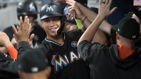 Miami Marlins' Giancarlo Stanton celebrates in the dugout after scoring against the Atlanta Braves during the ninth inning of a baseball game, Friday, Sept. 8, 2017, in Atlanta. Miami won 7-1. (AP Photo/John Amis)