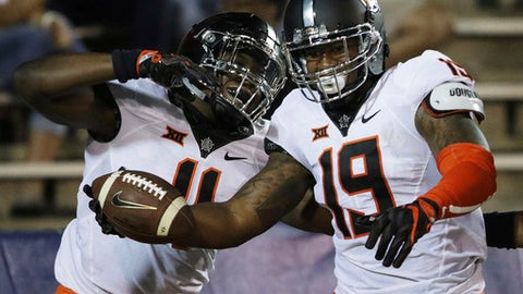 Oklahoma State linebacker Justin Phillips, right, celebrates his interception return for a touchdown against South Alabama with linebacker Amen Ogbongbemiga, during the second half of an NCAA college football game, Friday, Sept. 8, 2017, in Mobile, Ala. Oklahoma State won 44-7. (AP Photo/Dan Anderson)