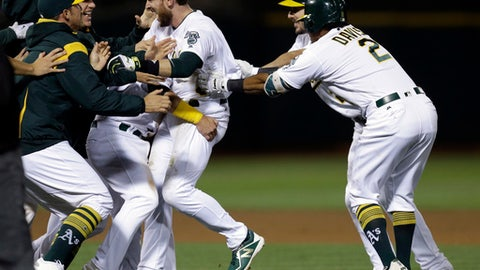 Oakland Athletics' Jed Lowrie, center, is mobbed by teammates after driving in the winning run against the Houston Astros in the ninth inning of a baseball game Friday, Sept. 8, 2017, in Oakland, Calif. The A's won 9-8. (AP Photo/Ben Margot)