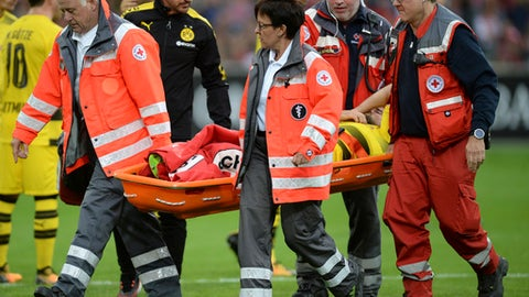 German Red Cross workers carry injured Dortmund player Marcel Schmelzer on a stretcher from the field during the German Bundesliga soccer match between SC Freiburg and Borussia Dortmund in the Schwarzwald stadium in Freiburg, Germany, Saturday, Sept. 9, 2017. (Patrick Seeger/dpa via AP)