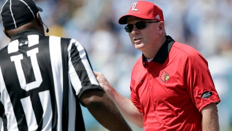 Louisville head coach Bobby Petrino speaks with an official during the first half of an NCAA college football game against North Carolina in Chapel Hill, N.C., Saturday, Sept. 9, 2017. (AP Photo/Gerry Broome)