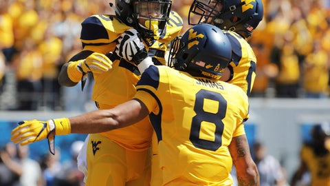West Virginia offensive lineman Colton McKivitz (53) and wide receiver Marcus Simms (8) celebrate with running back Justin Crawford (25) after he ran the ball for a touchdown during the first half of an NCAA college football game, Saturday, Sept. 9, 2017, in Morgantown, W.Va. (AP Photo/Raymond Thompson)