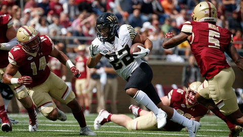 Wake Forest running back Matt Colburn (22) rushes past Boston College defenders during the first half of an NCAA college football game, Saturday, Sept. 9, 2017, in Boston. (AP Photo/Mary Schwalm)