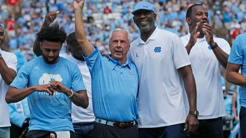 North Carolina men's basketball coach Roy Williams, center, waves to the crowd after he was presented his championship ring by former UNC and NBA great James Worthy, right, during a halftime ceremony of an NCAA college football game between Louisville and UNC, Saturday, Sept. 9, 2017, in Chapel Hill, N.C. (Chris Seward/The News & Observer via AP)