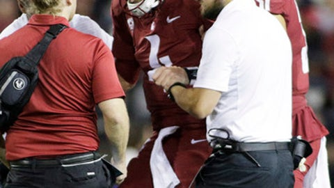 Washington State quarterback Luke Falk (4) is helped up by team staff after suffering an injury during the second half of an NCAA college football game against Boise State in Pullman, Wash., Saturday, Sept. 9, 2017. Washington State won 47-44. (AP Photo/Young Kwak)