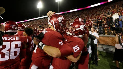 Washington State quarterback Tyler Hilinski, left, and quarterback Trey Tinsley (10) celebrate their team's 47-44 third overtime win over Boise State in an NCAA college football game in Pullman, Wash., Saturday, Sept. 9, 2017. (AP Photo/Young Kwak)
