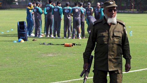 A Pakistani police officer stands guard while cricketers attend a training session for the upcoming World XI series at a ground in Lahore, Pakistan, Sunday, Sept. 10, 2017. Pakistan is preparing to show the cricketing world that it's safe to play international matches in the country by staging a three-match Twenty20 international series named World XI with players from seven countries in Lahore next week. (AP Photo/K.M. Chaudary)