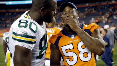 FILE - In a Saturday, Aug. 26, 2017 file photo, Denver Broncos outside linebacker Von Miller (58) greets Green Bay Packers tight end Martellus Bennett (80) after an NFL preseason football game, in Denver. Von Miller has sacked Philip Rivers more than any other quarterback in the NFL. That's not why he's delighted to open the season Monday night, Sept. 11,  when the Los Angeles Chargers visit the Denver Broncos.  (AP Photo/Jack Dempsey, File)