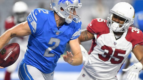 Detroit Lions punter Kasey Redfern (2) runs the ball out of the end zone as Arizona Cardinals running back Elijhaa Penny (35) pursues during the first half of an NFL football game in Detroit, Sunday, Sept. 10, 2017. (AP Photo/Jose Juarez)