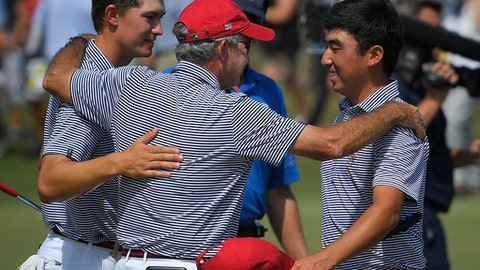 Captain Spider Miller, center, of the United States, embraces Maverick McNealy, left, and Doug Ghim after they completed their round during foursomes at the Walker Cup golf matches at Los Angeles Country Club, Sunday, Sept. 10, 2017, in Los Angeles. (AP Photo/Mark J. Terrill)