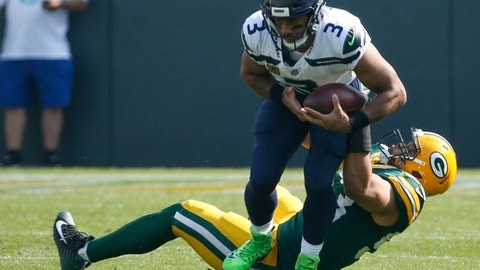 Seattle Seahawks' Russell Wilson gets away from Green Bay Packers' Nick Perry during the first half of an NFL football game Sunday, Sept. 10, 2017, in Green Bay, Wis. (AP Photo/Mike Roemer)
