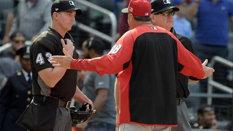 Cincinnati Reds manager Bryan Price (38) talks with umpire Shane Livensparger (43) and Jerry Layne during the seventh inning of a baseball game against the New York Mets, Sunday, Sept. 10, 2017, in New York. (AP Photo/Bill Kostroun)