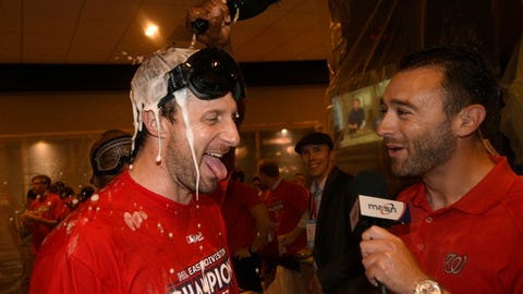 Washington Nationals Max Scherzer, left, is doused as he is interviewed in the locker room as the team celebrates after they clinched the National League East title after a baseball game against the Philadelphia Phillies, Sunday, Sept. 10, 2017, in Washington. (AP Photo/Nick Wass)