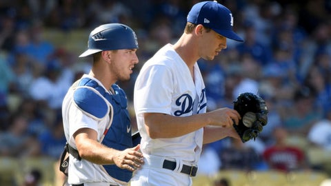 Los Angeles Dodgers catcher Austin Barnes goes to the mound with pitcher Walker Buehler during a jam in the eighth inning of a baseball game against the Colorado Rockies, Sunday, Sept. 10, 2017, in Los Angeles. (AP Photo/Michael Owen Baker)