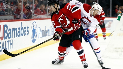 New Jersey Devils defenseman Damon Severson, left, and Montreal Canadiens left wing Paul Byron (41) compete for the puck during the first period of an NHL hockey game, Friday, Jan. 20, 2017, in Newark, N.J. (AP Photo/Julio Cortez)