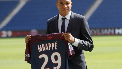 FILE - In this file photo dated Wednesday, Sept. 6, 2017, French soccer player Kylian Mbappe poses with his Paris Saint-Germain team shirt following a press conference in Paris.  The elite teams enter the Champions League competition this week, when the group stage begins, even while UEFA are combing through the Paris Saint-Germain finances, deciding whether to punish the French club for flouting spending rules to sign new players Neymar and Kylian Mbappe, but the .(AP Photo/Christophe Ena, FILE)