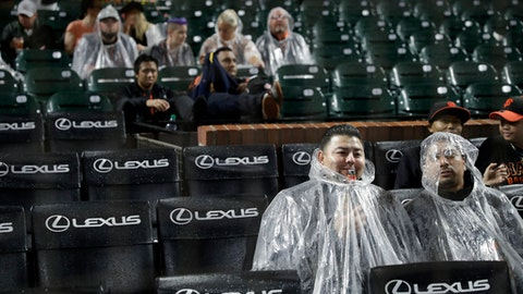 Fans cover themselves from the rain during a baseball game between the San Francisco Giants and the Los Angeles Dodgers, Monday, Sept. 11, 2017, in San Francisco. (AP Photo/Marcio Jose Sanchez)