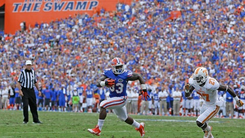 FILE - In this Sept. 21, 2013, file photo, then-Florida running back Mack Brown (33) runs a 3-yard touchdown past Tennessee defensive back Justin Coleman (27) during the first half of an NCAA college football game in Gainesville, Fla. After inspecting the stadium, meeting with campus and city officials, and assessing available resources, Florida decided its Southeastern Conference opener against Tennessee would be played as scheduled. So it's game on in Gainesville. The SEC announced Tuesday, Sept. 12, 2017, that the league opener between the No. 23 Volunteers (2-0) and the 24th-ranked Gators (0-1) will remain a 3:30 p.m. kickoff at Florida Field on Saturday, Sept. 16, 2017, keeping the game intact less than a week after Hurricane Irma devastated parts of the Sunshine State. (AP Photo/John Raoux, File)