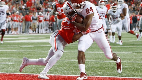 In this Saturday, Sept. 9, 2017 file photo, Oklahoma receiver Lee Morris, right, scores a touchdown as he is hit by Ohio State safety Erick Smith during the second half of an NCAA college football game, in Columbus, Ohio. Receiver Lee Morris, a sophomore walk-on, leads the team with two touchdown receptions on two catches. His 18-yard scoring grab in the third quarter against Ohio State gave the Sooners the lead for good.  (AP Photo/Jay LaPrete, File)
