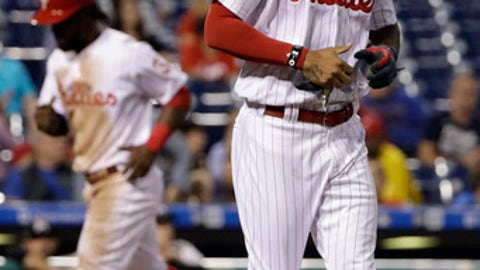 Philadelphia Phillies' Nick Williams, right, jogs to first base after being hit by a pitch from Miami Marlins starting pitcher Dillon Peters with the bases loaded which forced in Odubel Herrera, left, during the third inning of a baseball game, Tuesday, Sept. 12, 2017, in Philadelphia. (AP Photo/Matt Slocum)