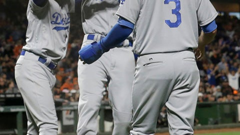 Los Angeles Dodgers' Curtis Granderson, left, celebrates after Cody Bellinger, center, and Chris Taylor (3) both scored on Yasiel Puig's two-run double against the San Francisco Giants during the fourth inning of a baseball game in San Francisco, Tuesday, Sept. 12, 2017. (AP Photo/Jeff Chiu)