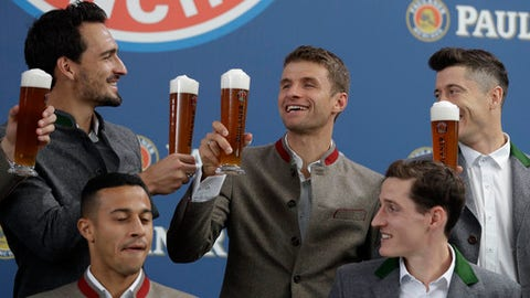 Bayern's Mats Hummels, left, and Robert Lewandowski, right, salut to team mate Thomas Mueller in traditional Bavarian clothes during a photo shooting of a beer brewing company in Munich, Germany, Wednesday, Sept. 13, 2017. Mueller celebrates his 28th birthday today. (AP Photo/Matthias Schrader)