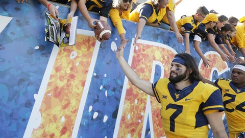 FILE - In this Saturday, Sept. 9, 2017, file photo, West Virginia quarterback Will Grier (7) celebrates their victory with fans at the conclusion of an NCAA college football game against East Carolina in Morgantown, W.Va.  Two years after a promising football career at Florida came crashing down, Will Grier is now the toast of West Virginia with two strong performances so far in the 2017 season. Yet he's not the most famous person in his family. Younger brothers Hayes and Nash are huge internet stars, building their own brands to millions of teenagers and young adults.(AP Photo/Raymond Thompson, File)