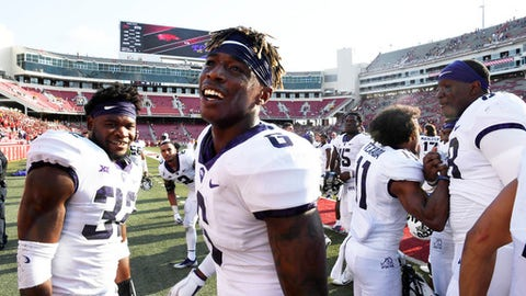 "FILE - In this Sept. 9, 2017, file photo, TCU players Travin Howard (32) and Innis Gaines (6) celebrate their win over Arkansas with teammates after an NCAA college football game in Fayetteville, Ark. Travin Howard and the rest of the TCU defenders don't worry about going from stifling a grind-it-on-the-ground offense one week to facing a big-passing team the next. ""You're just trusting in coach Gary Patterson's way,"" the Horned Frogs' top tackler said. (AP Photo/Michael Woods, File)"