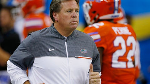 FILE - In this Saturday, Dec. 3, 2016 file photo, Florida head coach Jim McElwain runs out on the field before the first half of the Southeastern Conference championship NCAA college football game between Alabama and Florida in Atlanta. Jim McElwain was somber and solemn Wednesday, Sept. 13, 2017 mirroring how millions of Floridians felt following Hurricane Irma. he Florida coach's tone surely resonated across the Sunshine State, which was dealing with displaced families, damaged homes, significant flooding and widespread power loss. He hopes his team's performance Saturday, Sept. 16, 2017 against 23rd-ranked Tennessee (2-0) will do the same. (AP Photo/Butch Dill, File)