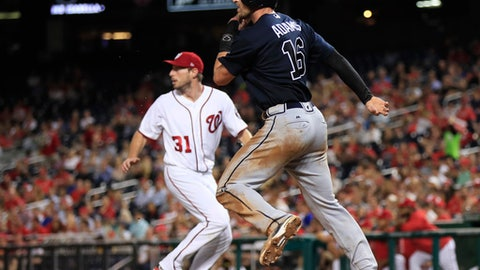 Atlanta Braves' Lane Adams (16) turns around and looks back for his teammate Jace Peterson running behind him, during the seventh inning of a baseball game against the Washington Nationals in Washington, Wednesday, Sept. 13, 2017. Adams and Peterson both scored on a single by Braves Dansby Swanson. Washington Nationals starting pitcher Max Scherzer (31) runs on back left. (AP Photo/Manuel Balce Ceneta)
