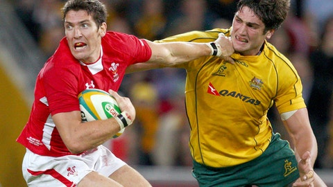FILE - In this June 9, 2012 file photo Wales' James Hook, left, fends off Australia's Rob Simmons during their rugby union test match at Brisbane, Australia. Australia's coach, Michael Cheika, said on Thursday, Sept. 14, 2017, said Simmons would line up for his 75th test cap against Argentina in Canberra, Saturday. (AP Photo/Rick Rycroft, FILE)
