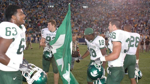 FILE - In this September 2005 file photo, Michigan State players Devin Pritchett (63), Nick Smith (93), Terry Love (18) and Eric Smith (36) plant a flag in the center of the field at Notre Dame Stadium following the team's 44-41 overtime victory in South Bend, Ind. Michigan State blew a 21-point before rallying. The victory spoiled the home debut of coach Charlie Weis and gave the Spartans five straight wins at Notre Dame Stadium, so few could blame them for celebrating at the Irish's 50-yard line. But Notre Dame got its revenge a year later, outscoring Michigan State 19-0 in East Lansing in the fourth quarter for a 40-37 victory. (AP Photo/Joe Raymond, File)