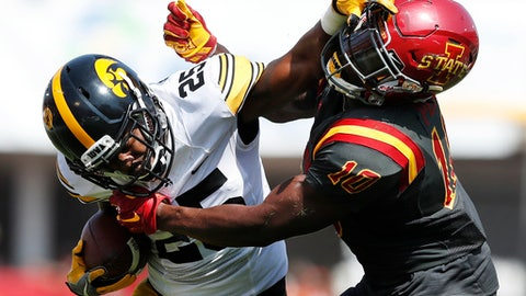 FILE - In this Sept. 9, 2017, file photo,Iowa running back Akrum Wadley (25) breaks a tackle by Iowa State defensive back Brian Peavy, right, during the first half of an NCAA college football game, in Ames, Iowa. Iowa plays North Texas on Saturday. (AP Photo/Charlie Neibergall, File)