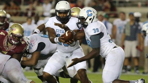 Citadel's Dominique Allen, left,  hands off to Isiaha Smith in a play against Florida Sate in an NCAA college football game Saturday, Sept. 6, 2014, in Tallahassee, Fla. Florida State won the game 37-12. (AP Photo/Steve Cannon)