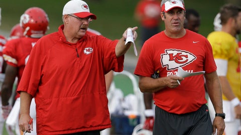 FILE - In this Aug. 17, 2015 file photo, Kansas City Chiefs head coach Andy Reid, left, and offensive coordinator Doug Pederson, right, talk during NFL football training camp in St. Joseph, Mo. Andy Reid gave Doug Pederson his first starting job in the NFL and later his first coaching gig, too. Pederson hopes to repay Reid with a loss. The student meets the teacher on Sunday, Sept. 17, 2017 when Pederson leads the Philadelphia Eagles (1-0) against Reid and the Kansas City Chiefs (1-0) at Arrowhead Stadium.  (AP Photo/Orlin Wagner, File)
