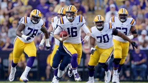 FILE - In this Sept. 9, 2017, file photo, LSU quarterback Danny Etling (16) scrambles for 17 yards and a first down during the first half of an NCAA college football game against Chattanooga in Baton Rouge, La. Etling isn't letting the size and speed of his receivers go to waste. He's been willing to throw deep - even into double coverage at times - and has been rewarded with big catches by receivers who'll likely face their toughest challenge yet at Mississippi State. (AP Photo/Rusty Costanza, File)
