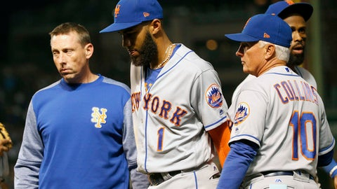 New York Mets' assistant trainer Brian Chicklo, left, and manager Terry Collins (10) pull Amed Rosario from the game in the middle of the fifth inning of a baseball game against the Chicago Cubs Thursday, Sept. 14, 2017, in Chicago. (AP Photo/Charles Rex Arbogast)