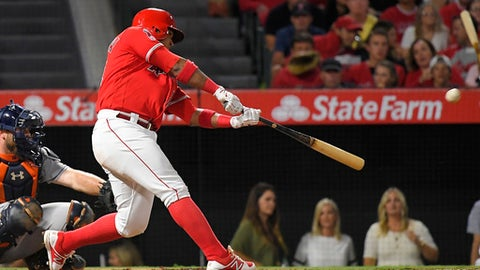 Los Angeles Angels' Luis Valbuena hits a solo home run in front of Houston Astros catcher Brian McCann during the fourth inning of a baseball game, Thursday, Sept. 14, 2017, in Anaheim, Calif. (AP Photo/Mark J. Terrill)