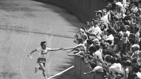 FILE - In this Aug. 29, 1978, file photo, Dave McGillivray reaches out to fans at Fenway Park in Boston, as he completes a 3,400-mile, 80-day cross country run to raise funds for a children's cancer research charity. Longtime Boston Marathon race director Dave McGillivray has organized an unusual inside Fenway Park Marathon. Friday's event will take 50 runners around the outfield of Boston's storied baseball stadium 116 times to cover the classic 26.2-mile distance. McGillivray says the race is the culmination of a dream he had as a boy when he aspired to play second base for the Red Sox. (AP Photo/Chip Maury, File)