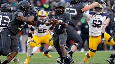 FILE - In this Dec. 10, 2016, file photo, Army quarterback Ahmad Bradshaw, center, drops back from the line of scrimmage in the first half against Navy in an NCAA college football game in Baltimore. Army, which plays at Ohio State this week, runs a confounding triple-option attack centered on Bradshaw, who is averaging 162 yards after two games to rank sixth nationally, and 9.5 yards per carry with three TDs. He has seven 100-yard games in his career. (AP Photo/Patrick Semansky, File)