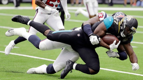 FILE - In this Sunday, Sept. 10, 2017, file photo, Jacksonville Jaguars running back Leonard Fournette (27) is tackled by Houston Texans defensive end Joel Heath (93) during the first half of an NFL football game in Houston. Of 266 rookies on active rosters in Week 1, 33 started and 13 more played at least half the snaps. Linebackers and running backs led the way with a combined total of 15 guys, including Kareem Hunt, Leonard Fournette and T.J. Watt. (AP Photo/David J. Phillip, File)
