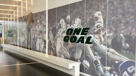 A mural is displayed on the wall of the players' entrance at the New York Jets NFL football training facility, Friday, Sept. 15, 2017, in Florham Park, N.J. Jets coach Todd Bowles went to work on changing the culture around the team this offseason by starting with the walls. The coach redecorated the hallways with photos of star players from the team's past, giving the current Jets something to strive for during a rebuilding season for the franchise (AP Photo/Dennis Waszak Jr.)