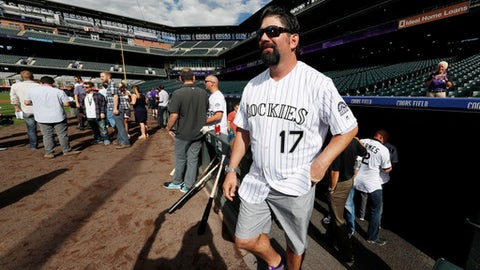 Retired Colorado Rockies first baseman Todd Helton (17) steps out of the dugout as members of the Rockies' 2007 Word Series team look on during batting practice before the Rockies host the San Diego Padres in a baseball game Friday, Sept. 15, 2017, in Denver. (AP Photo/David Zalubowski)
