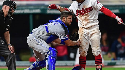 Kansas City Royals catcher Drew Butera, center, tags out Cleveland Indians Francisco Lindor, right, in the ninth inning of a baseball game, Friday, Sept. 15, 2017, in Cleveland. (AP Photo/David Dermer)
