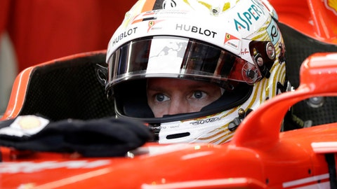Ferrari driver Sebastian Vettel of Germany waits in his car during the third practice session at the Singapore Formula One Grand Prix on the Marina Bay City Circuit Singapore, Saturday, Sept. 16, 2017. (AP Photo/Wong Maye-E)