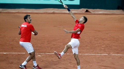 Filip Krajinovic, left, and Nenad Zimonjic of Serbia return the ball to Pierre-Hugues Herbert and Nicolas Mahut of France during their double Davis Cup semi final match at the Pierre Mauroy stadium in Lille, northern France, Saturday, Sept.16, 2017. (AP Photo/Michel Spingler)