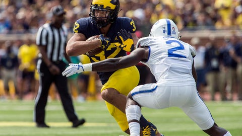 Michigan running back Ty Isaac (32) rushes as Air Force defensive back Marquis Griffin (2) defends in the second quarter of an NCAA college football game in Ann Arbor, Mich., Saturday, Sept. 16, 2017. (AP Photo/Tony Ding)