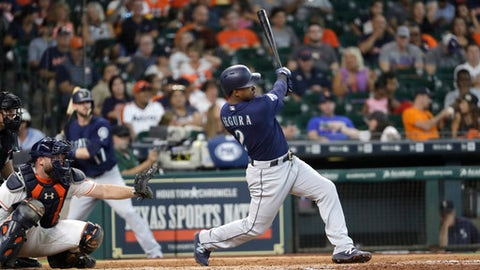 Seattle Mariners' Jean Segura (2) hits a home run as Houston Astros catcher Brian McCann reaches for the pitch during the sixth inning of a baseball game Saturday, Sept. 16, 2017, in Houston. (AP Photo/David J. Phillip)