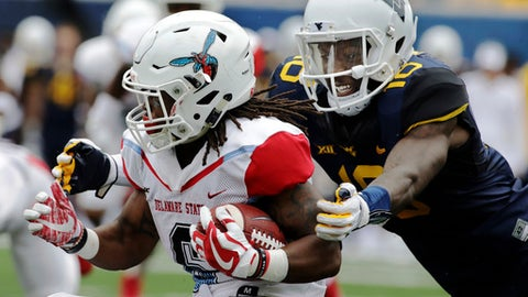 Delaware State running back Brycen Alleyne (6) is tackled from behind by West Virginia safety Marvin Gross Jr. (18) during the second half of an NCAA college football game, Saturday, Sept. 16, 2017, in Morgantown, W.Va. West Virginia defeated Delaware State 59-16. (AP Photo/Raymond Thompson)